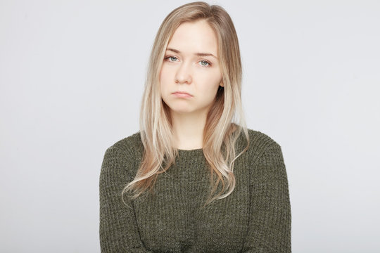 Bewildered displeased sorrowful woman going to cry as sees no way out in difficult life situation, scowls face and curves lips, expresses negative emotions, isolated over white studio background.