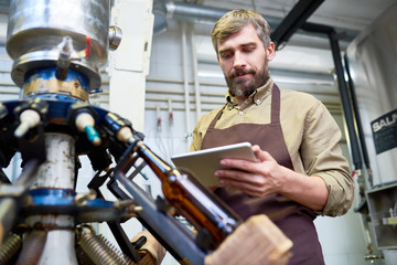Portrait of middle-aged technician with bushy beard studying operation manual with help of digital tablet while standing at beer bottling equipment