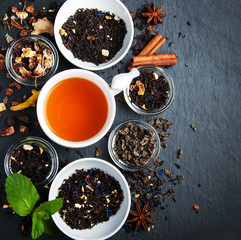 Cup of tea with aromatic dry tea in bowls