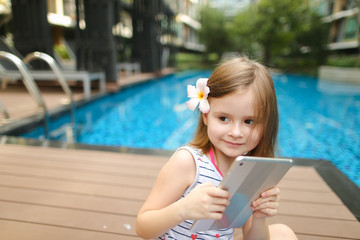little kid girl taking selfie on tablet sitting close to blue swimming pool wearing flower and hold toy. concept of new technology or travel recreation, holiday family time on sunny day