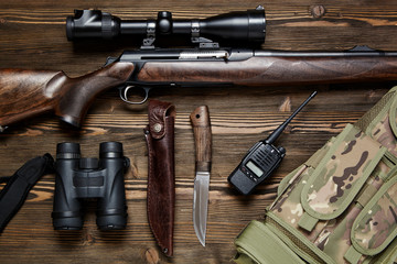 Hunting rifle and ammunition on a wooden background.