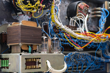 Transformer, radio tubes and wires. Old radio lamp device. Lamp receiver. Inside view. Selective focus