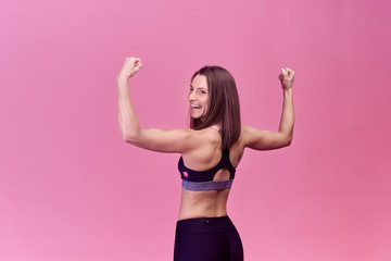 Portrait of a strong beautiful woman from behind with muscles and happy joyful emotion.