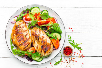 Poster Kip Grilled chicken breast. Fried chicken fillet and fresh vegetable salad of tomatoes, cucumbers and arugula leaves. Chicken meat salad. Healthy food. Flat lay. Top view. White background