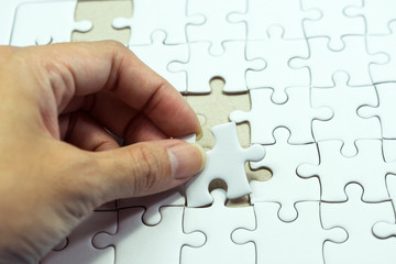 Hand holding jigsaw for connect puzzle game on frame background. Concept business or education.