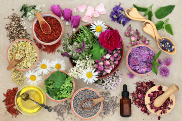 Herbal medicine preparation with herbs and flowers, aromatherapy essential oil bottle and mortar with pestle on hemp paper background. Top view.
