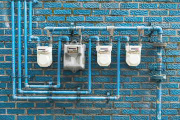 Several gas meters located on the wall of a residential building
