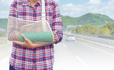 broken arm with green cast and arm sling isolated on blurred cars run on a Japanese highway with mountain background, insurance concept