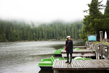 Asian thai woman travel and walking at Waterfront wooden bridge at Mummelsee lake while raining in Black Forest or Schwarzwald in Germany