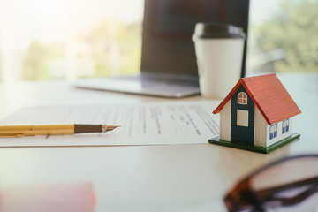 Contract for house sale or insurance with pen in a real estate concept.