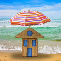 Small wooden house at seaside with umbrella beach - concept image