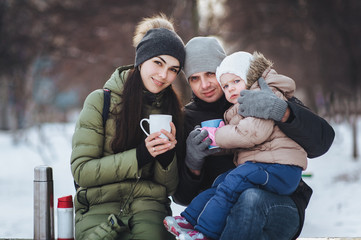 Young parents with their little daughter drinks hot tea from a thermos in the winter. Happy young family on snow background. Winter walk.