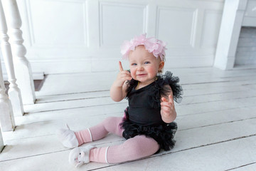 Little smiling baby girl one year old with wreath crawl on the floor in bright room and laughs. Happy kid playing at home