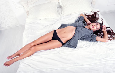 Gorgeous sexy young woman in panties and shirt lying on bed