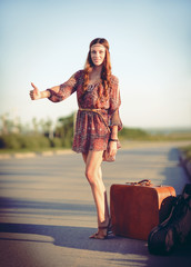Attractive smiling young hippie woman hitchhiking on a road at sunset time