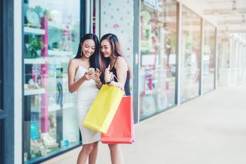 Happy women using phone Enjoying Spending shopping bags in Fashion shopping street