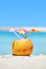 Close up picture of a coconut with two straws and colorful umbrella on a beach, summer holiday concept, selective focus.