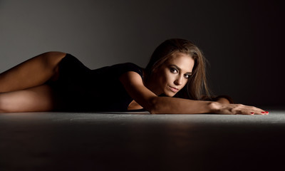 Young happy beautiful sexy woman posing lying in summer fashion leather black body cloth
