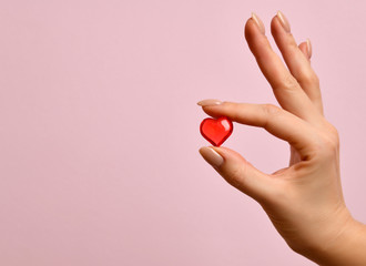 Woman hand hold little red heart on pink