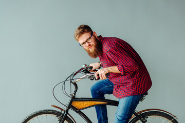 Artistic concept. Creative beard man on retro bicycle looking at camera over grey background.