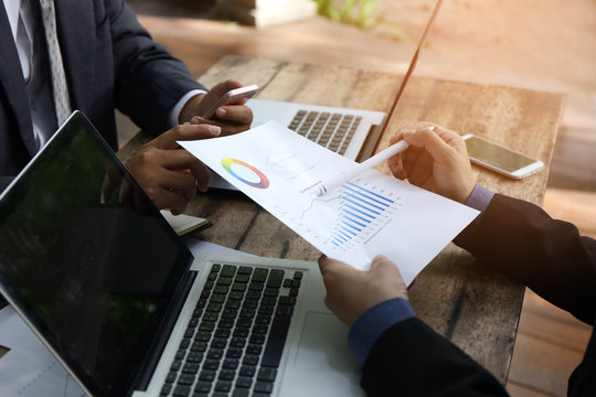 banker businessman people group working with laptop and financial document chart on wood table together.