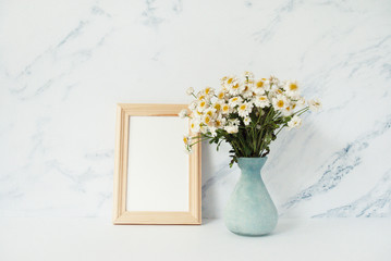Wooden photo frame mockup, bouquet of white chamomile in front of pale marble pastel background