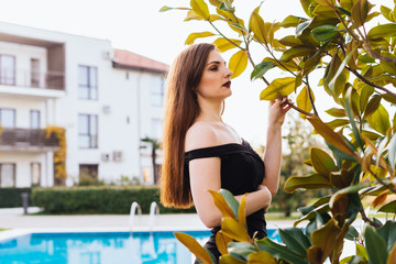 beautiful long-haired attractive woman in a black dress walking around her garden, enjoying nature
