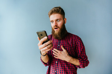 Hipster beard caucasian man with different surprising emotions holding smart phone on blue background.