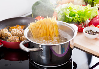 Cooking spaghetti in a pot with boiling water