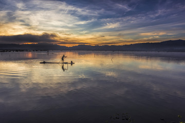 Fisherman silhouette with bamboo raft in water lake