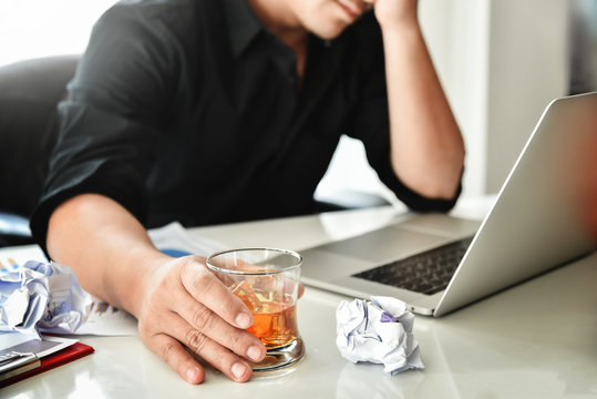 Alcohol addicted businessman is holding whiskey glass.
