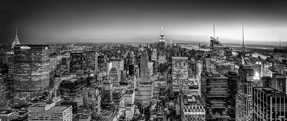 Fototapete - New York City. Manhattan downtown skyline with illuminated Empire State Building and skyscrapers at dusk. USA. Black and white image.