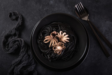 squid ink spaghetti pasta with octopuses in black bowl