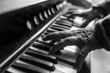 Elderly musician playing a piano indoors