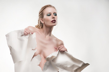 Beautiful topless girl tears a large sheet of white whatman paper and covers with it her naked breast.