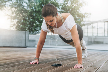 Summer day. Young woman doing sports exercises outdoors. Girl makes plank while looking at smartphone screen and listening to music. Workout, sports, sports training.
