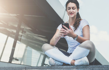 Summer day. Young woman athletes in white sports clothes are sitting in city street, relax after sports training, use smartphone, listen to music. Girl checking email, browsing internet, chatting.