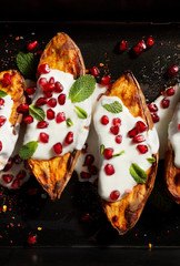 Baked sweet potatoes with garlic mint yogurt sauce sprinkled with pomegranate seeds and fresh mint leaves on a black stone background . Delicious and healthy vegetarian meal