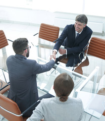 Handshake across the table of financial partners