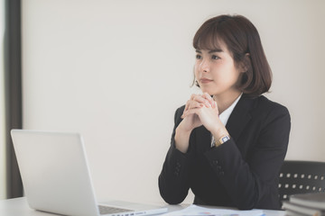 Young Asian woman working at a desk in business sector