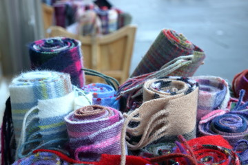 Pozwijane w ruloniki szaliki, kolorowe, w drobne paski, w kratę, ciepłe, wełniane, niektóre rozmyte, w drewnianych skrzyniach przed wystawą sklepową, na ulicy