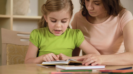 Girl reading interesting storybook for mother, woman proud of smart daughter