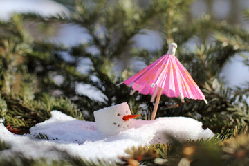 spring weather warming/ head of snowman in a melting snowdrift under red umbrella is hiding from the sun