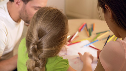 Family drawing colorful pictures with pencils, parents enjoying time with kid