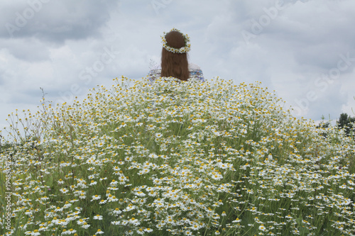 feb7ddd07c23 girl in white dress in chamomile field on a cloudy summer day