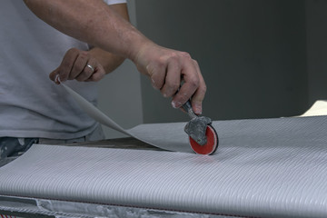 Renovation or refurbishment. Preparation of wallpaper with glue with a construction tools glue maker. Concept: painter craft or construction site