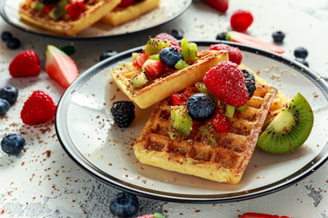Fresh egg waffles dessert for breakfast with fruits strawberries, blueberries, blackberries, raspberries and kiwi
