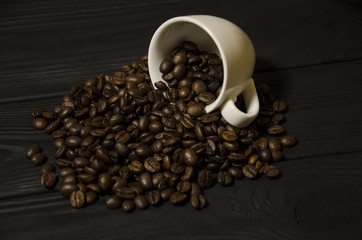 Grains of coffee and a cup on a black, wooden background.