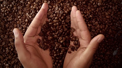 man hand hold coffee beans and then throw it down. Top view