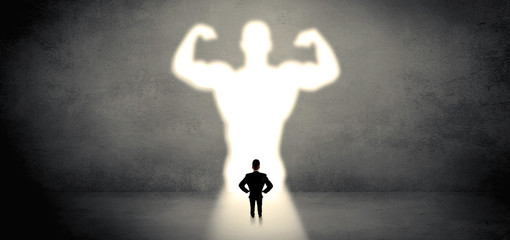 Businessman standing in front of a strong hero vision